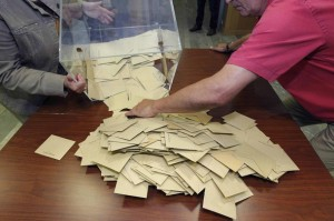 Election officials empty a ballot box to count votes from the first round of the parliamentary election in a polling station in Vertou